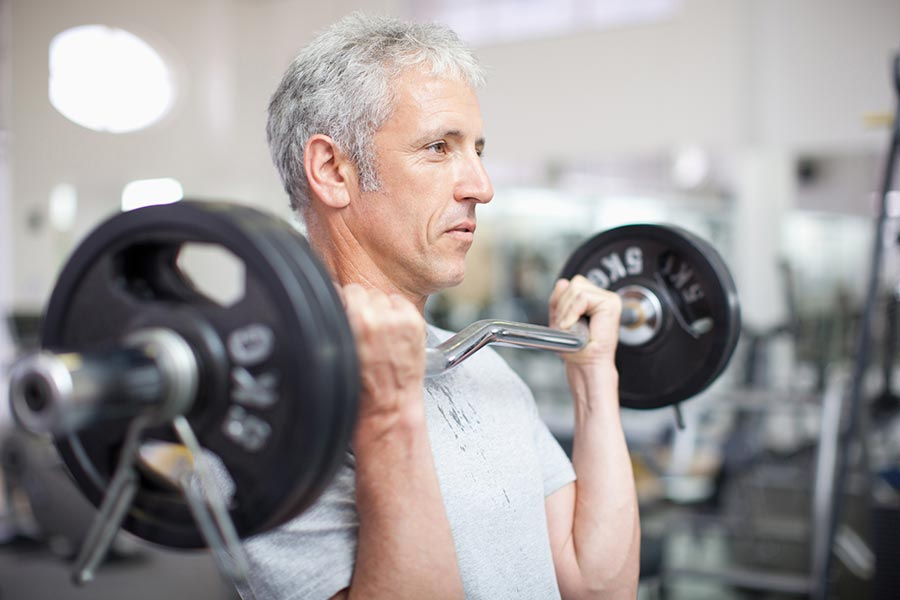 man holding barbell in gymnasium